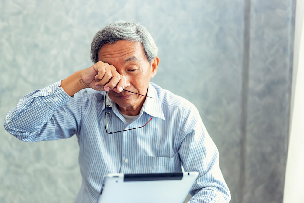 man rubbing his eyes, macular degeneration awareness month at new jersey eye center bergenfield