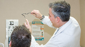 Dr. James Dello Russo consulting his patient about his glasses