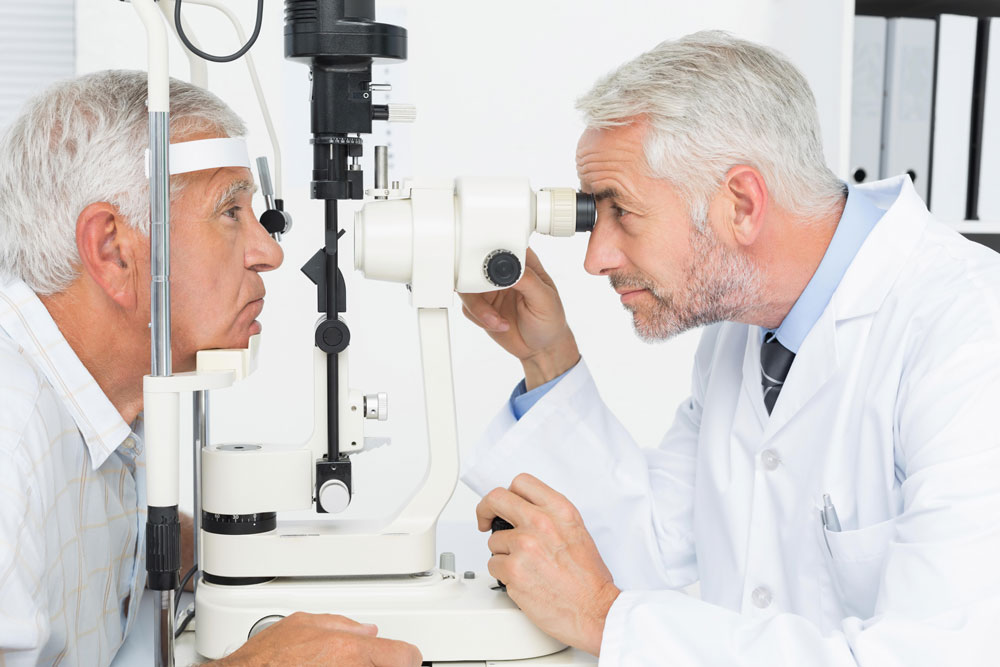 Optometrist doing sight testing for senior patient to determine his cataract surgery options.